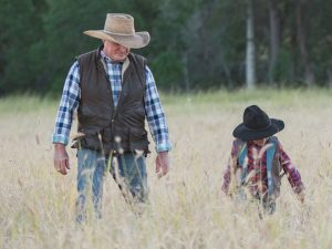 Father and son walking through long grass